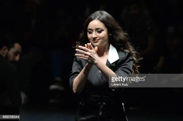 Designer Neslihan Comez acknowledges the applause of the audience after her 'Hide Your Inverse' show as part of the New GEN by IMA show during...