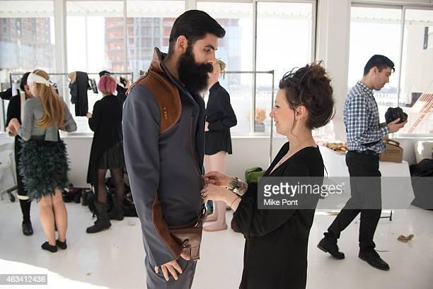 Designer Nina Athanasiou helps a model prepare backstage at the Nina Athanasiou fashion show during Mercedes Benz Fashion Week Fall 2015 at The...