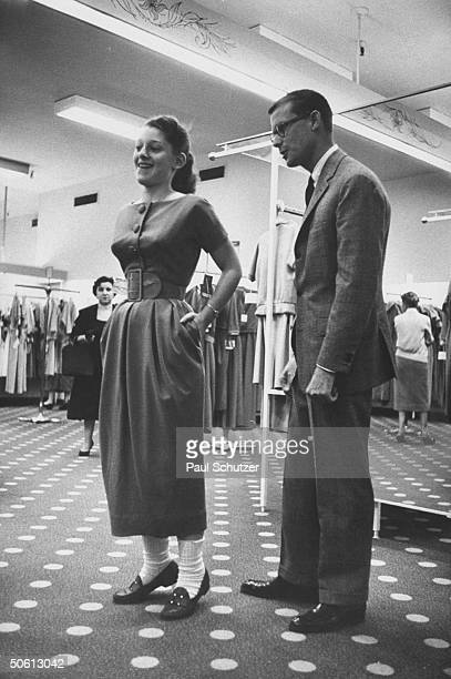 Designer Ole Borden watching as teenager tries on dress w new longer length skirt inspired by designer Christian Dior at Bloomingdale's