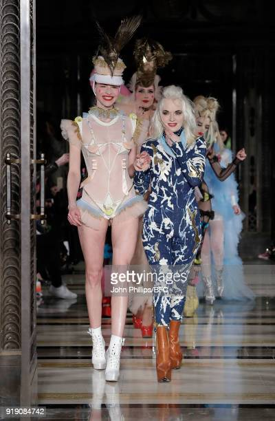 Designer Pam Hogg and a model walk the runway at the Pam Hogg show during London Fashion Week February 2018 at The Freemason's Hall on February 16...
