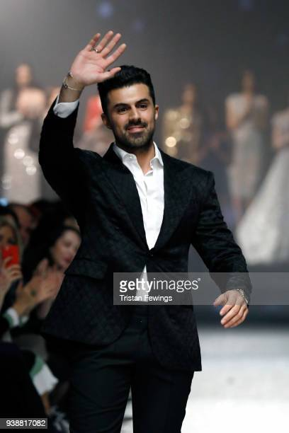 Designer Rasit Bagzibagli acknowledges the applause of the audience after his show during MercedesBenz Fashion Week Istanbul at Shangri La Hotel...