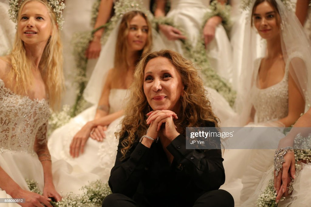 Designer Reem Acra poses with models at the conclusion of her Reem Acra FW 2018 Bridal Show at the New York Public Library on October 5, 2017 in New York City.