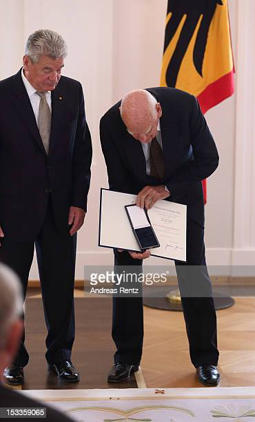 Designer Richard Sapper reacts after his Federal Cross of Merit falls down he received from German President Joachim Gauck at Bellevue Palace on...