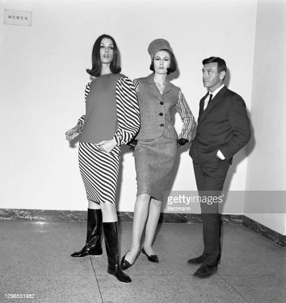 Designer Rudi Gernreich poses with two of his creations, a two-piece wool knit dress with red bodice and black and white strips and a black and white...
