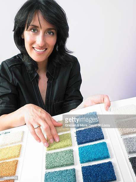 Designer showing carpet samples to camera.