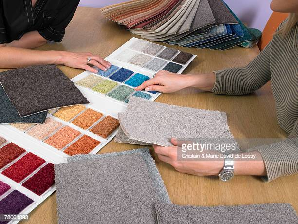 Designer showing carpet samples to client.