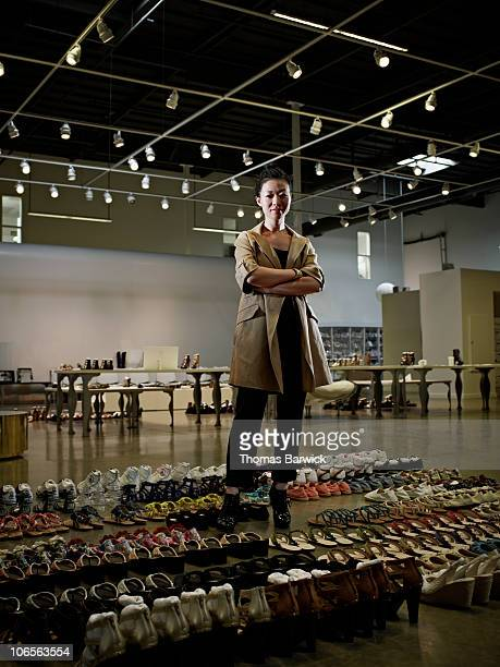 Designer standing in showroom surrounded by shoes