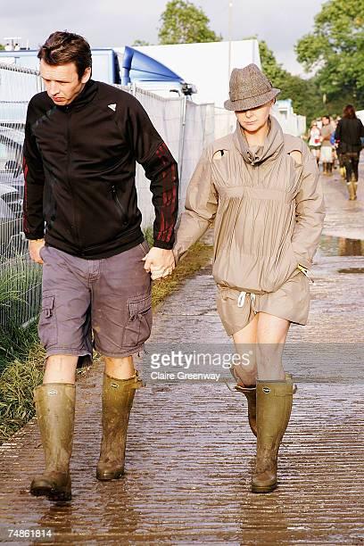 Designer Stella McCartney and her husband Alasdhair Willis walk backstage on the first day of the Glastonbury Festival at Worthy Farm Pilton near...