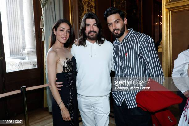 Designer Stephane Rolland poses between Sofia Essaidi and her husband Adrien Galo after the Stephane Rolland Haute Couture Fall/Winter 2019 2020 show...