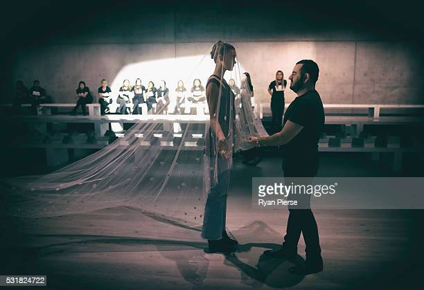 Designer Steven Khalil prepares with a model ahead of his show during the Akira show during MercedesBenz Fashion Week Australia at Carriageworks on...