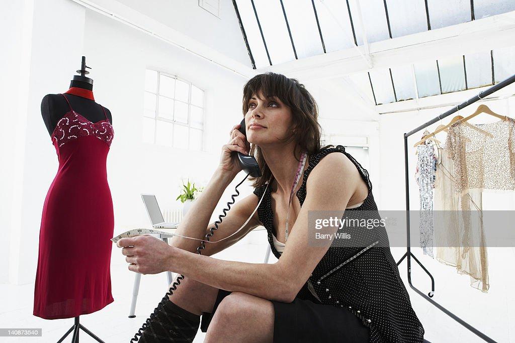 Designer talking on phone in studio : Bildbanksbilder