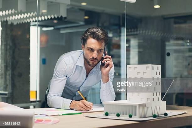 Créateur parler sur le téléphone intelligent dans le bureau.