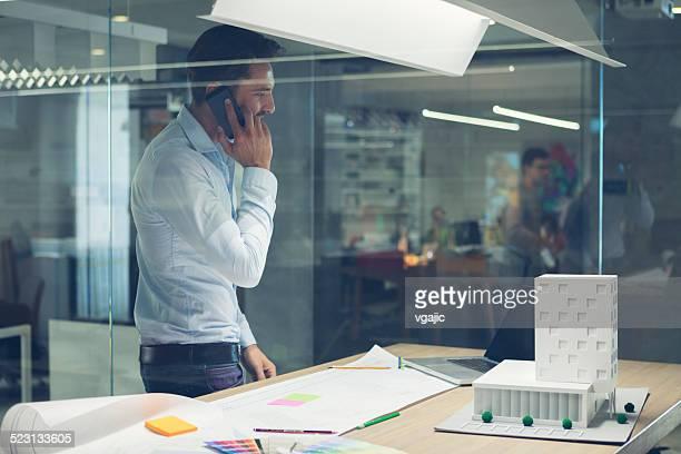 Diseñador hablando por teléfono inteligente en oficina.