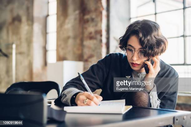 designer talking on telephone at work - one young woman only stock pictures, royalty-free photos & images