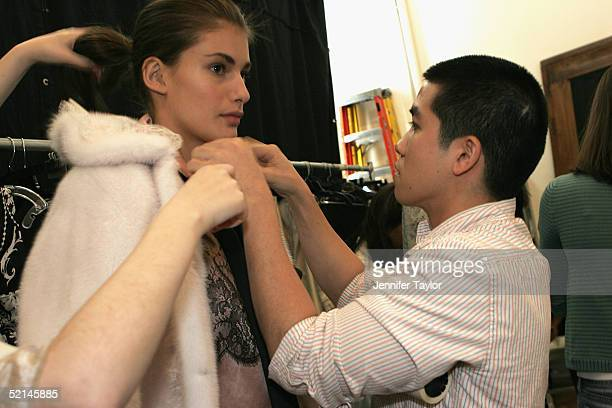 Designer Thakoon Panichgul gets a model ready backstage at the presentation of the Thakoon Fall 2005 show during Olympus Fashion Week at DriveIn...