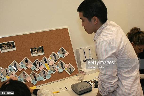 Designer Thakoon Panichgul looks at a polaroid board of model's pictures backstage at the presentation of the Thakoon Fall 2005 show during Olympus...