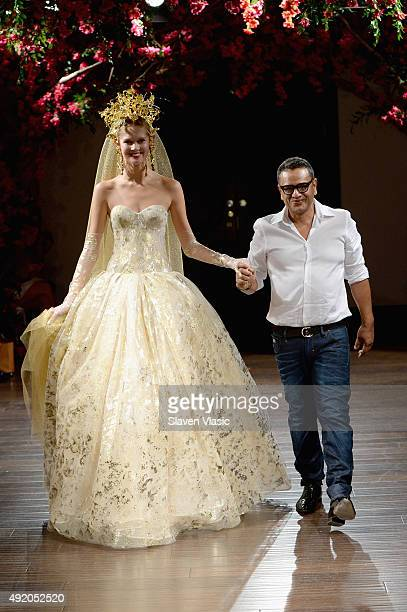 Designer the Naeem Khan walks the runway with a model during the Naeem Khan Bridal Fall/Winter 2016 show on October 9 2015 in New York City