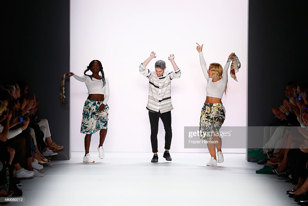 Designer Timm Suessbrich (L) and Nikeata Thompson (C) dance on the Barre Noire presented by Mastercard show during the Mercedes-Benz Fashion Week Berlin Spring/Summer 2016 at Brandenburg Gate on July 9, 2015 in Berlin, Germany.