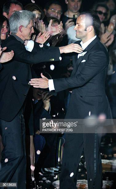"""Designer Tom Ford embraces his partner Richard Buckley, editor in chief of """"Vogue Hommes International"""" as he acknowledges applause on the catwalk at..."""