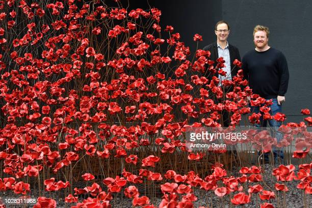 Designer Tom Piper and artist Paul Cummins pose with the iconic poppy sculpture 'Wave' as it opens at IWM North it's final presentation as part of...