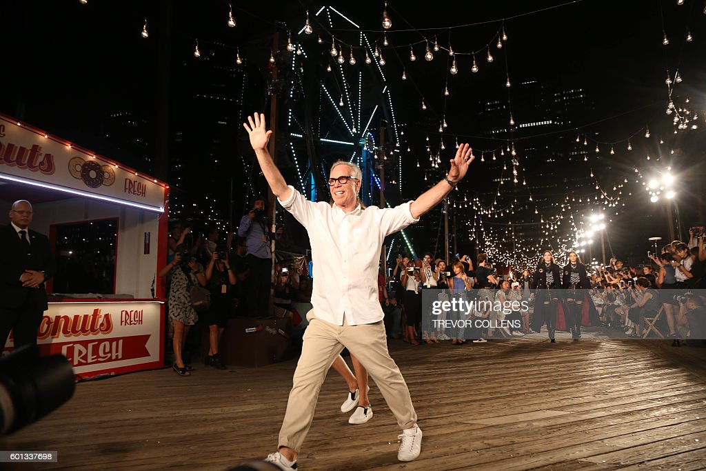 Designer Tommy Hilfiger waves to the audience during the Tommy Hilfiger fall 2016 collection presented at New York Fashion Week in New York, September 9, 2016. / AFP / TREVOR