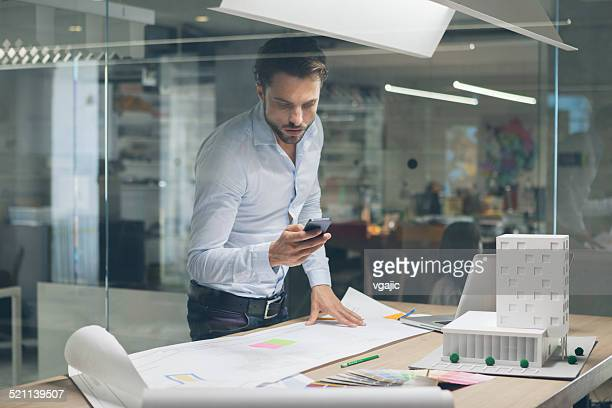 Designer Tippen auf Handy im Büro.
