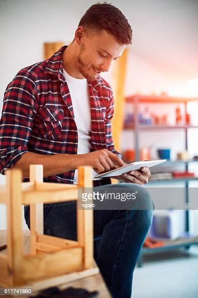 """Créateur de mode à l'aide de tablette numérique dans son mobilier """" atelier."""