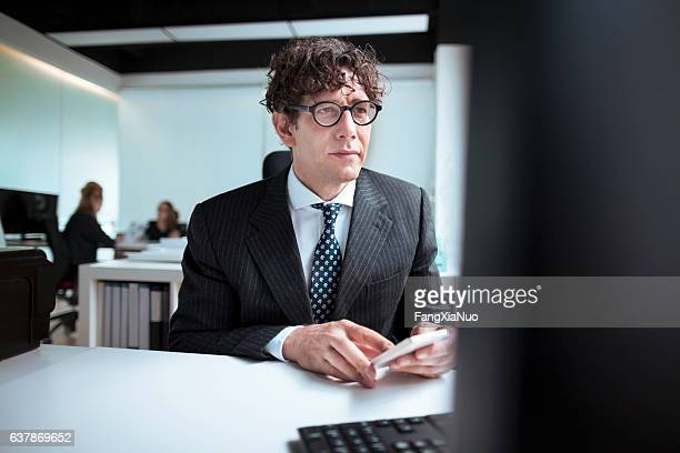 Designer using smart phone and computer in office