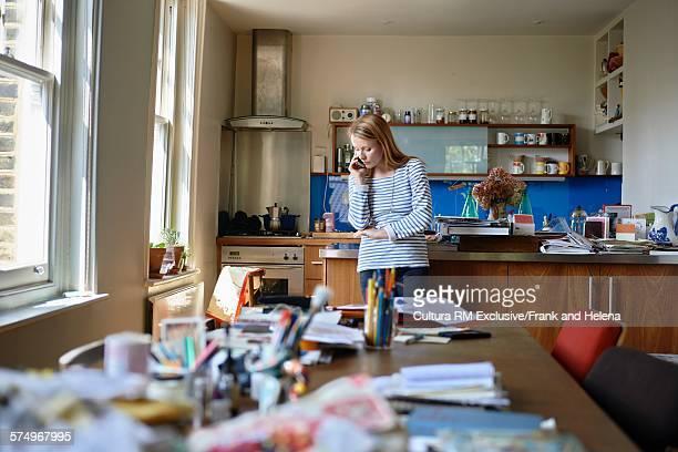 Designer using smartphone in kitchen