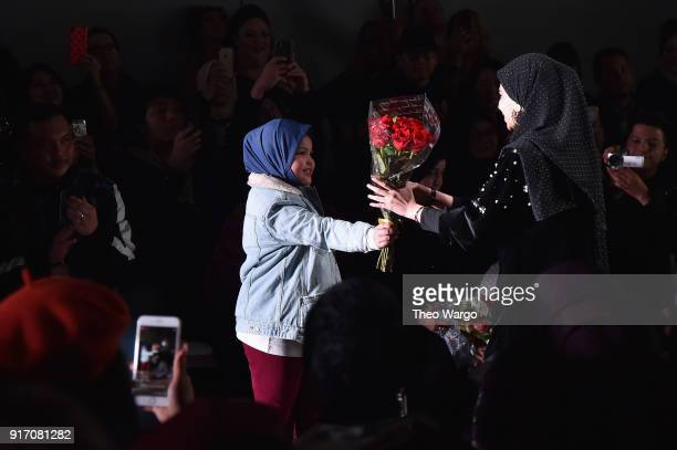 Designer Vivi Zubedi receives roses from a guest at the Vivi Zubedi front row during New York Fashion Week The Shows at Industria Studios on February...