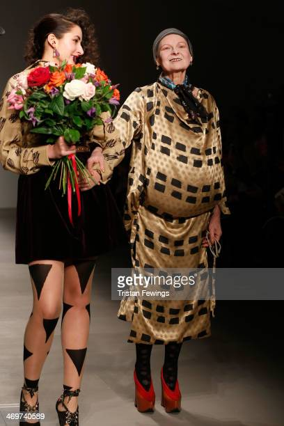Designer Vivienne Westwood walks with a model on the runway after the Vivienne Westwood Red Label show at London Fashion Week AW14 at on February 16...