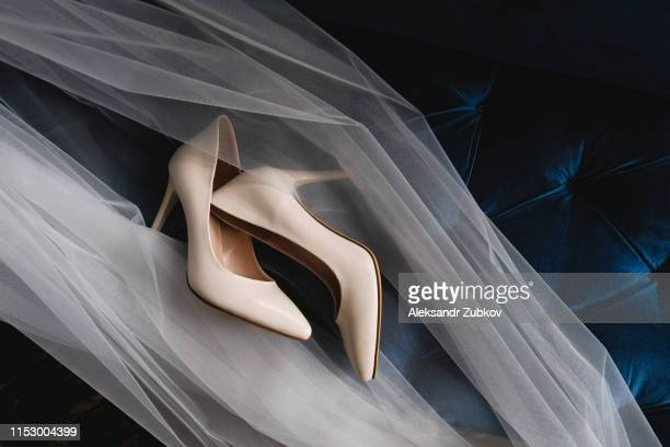 designer wedding beige bride shoes on an expensive velour sofa, tulle or veil. women's new modern fashion high-heeled shoes, genuine leather. morning preparations for the wedding. - chaussures beiges photos et images de collection
