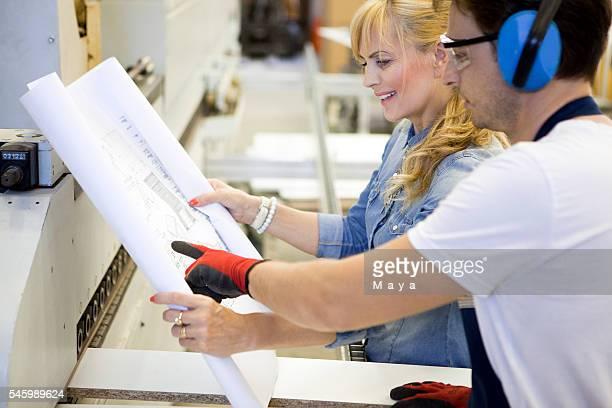 Designer with worker at furniture workshop