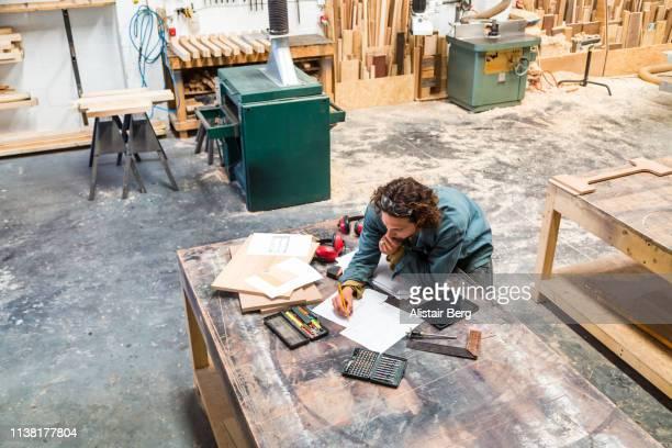 designer working at a bench in a furniture factory - designer einrichtung stock-fotos und bilder