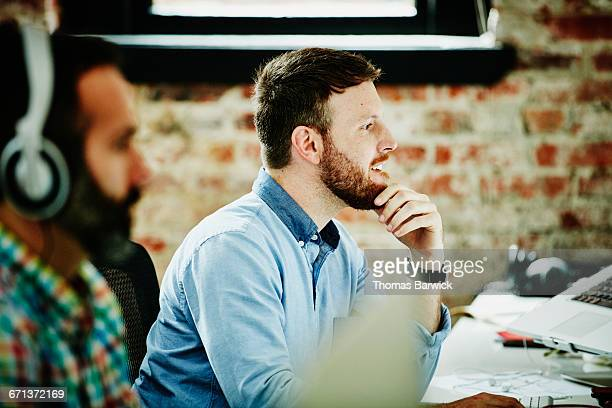Designer working on computer at desk in office