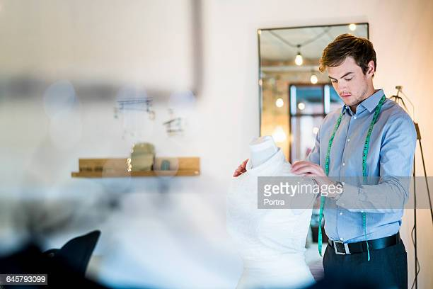 Designer working on wedding gown in bridal shop