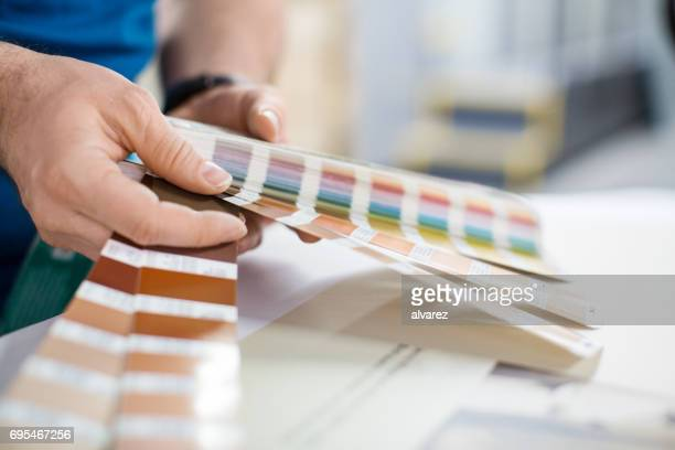 Designer working with color palette at printing press