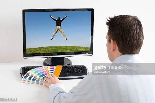 Designer works in front of computer using color picker