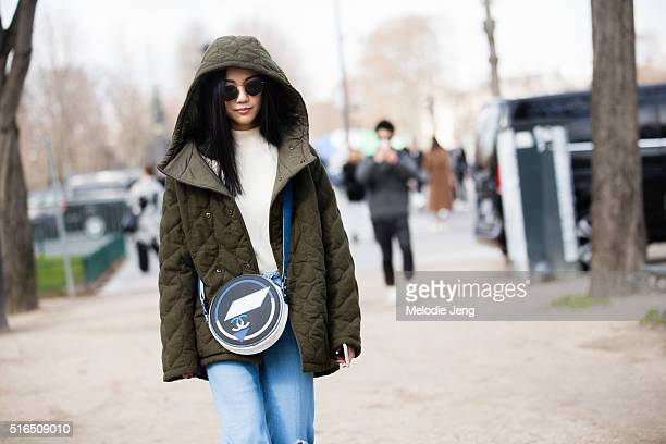 Designer Yoyo Cao wears an oversized olive quilted coat with a hood a blue circular Chanel purse distressed flared jeans and white heels after the...