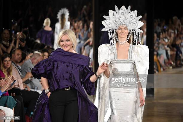 Designer Yulia Yanina acknowledges the audience with a model during the Yanina Couture Haute Couture Fall Winter 2018/2019 show as part of Paris...