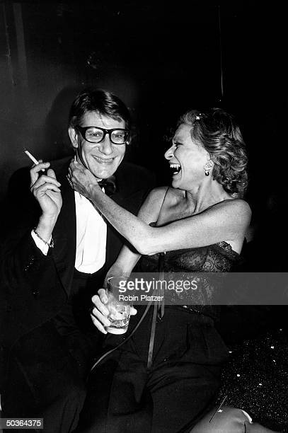Designer Yves Saint Laurent w. Socialite Nan Kempner during party for the launching his new perfume called Opium, held aboard the sailboat Peking at...