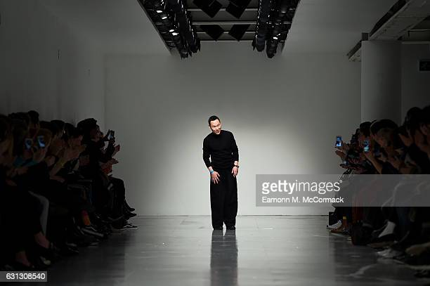 Designer Zio Song salutes the crowd following the SONGZIO show during London Fashion Week Men's January 2017 collections at BFC Show Space on January...