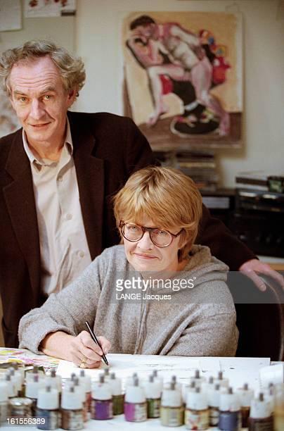 Designers Claire Bretecher And Rene Petillon les dessinateurs Claire BRETECHER un feutre à la main assise à sa table de dessin et René PETILLON posant