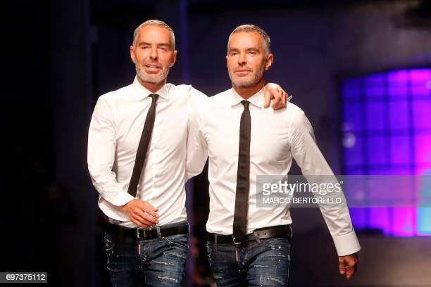 Designers Dean Caten and Dan Caten greet the audience at the end of their show for fashion house Dsquared2 during the Men's Spring/Summer 2018...