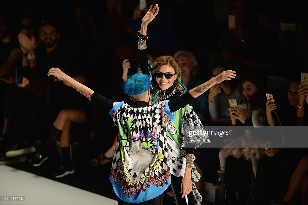 Designers, Deniz Berdan (R) and Begum Berdan are applauded walks the runway at the DB Berdan show during Mercedes-Benz Fashion Week Istanbul at Zorlu Center on October 13, 2016 in Istanbul, Turkey.