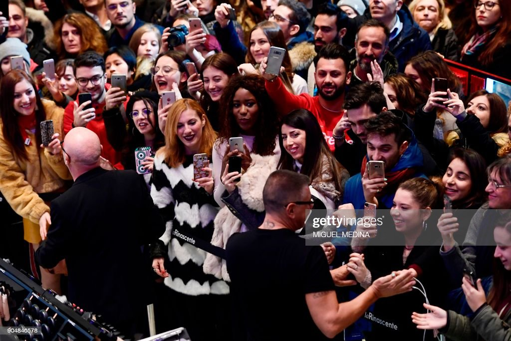 Designers Domenico Dolce (L) and Stefano Gabbana greet fans at the end of their public show at La Rinascente department store as part of Men's Fall/Winter 2019 fashion shows in Milan, on January 14, 2018. / AFP PHOTO / Miguel MEDINA