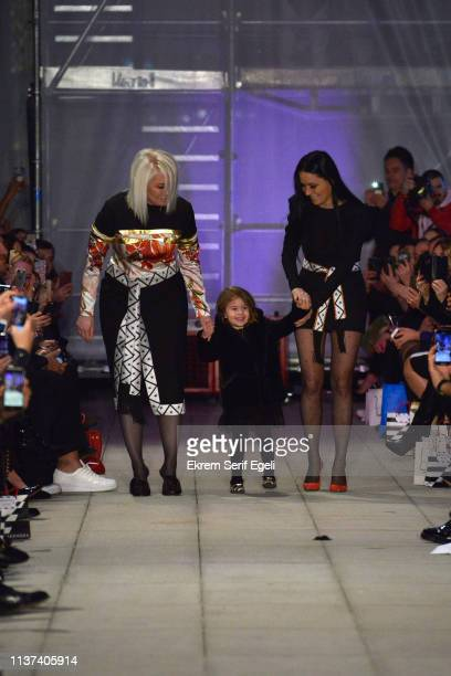 Designers Ezra Cetin and Tuba Cetin acknowledge the applause of the audience after the Ezra Tuba show during MercedesBenz Istanbul Fashion Week on...