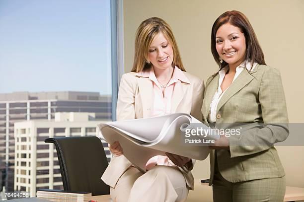 Designers holding blueprints