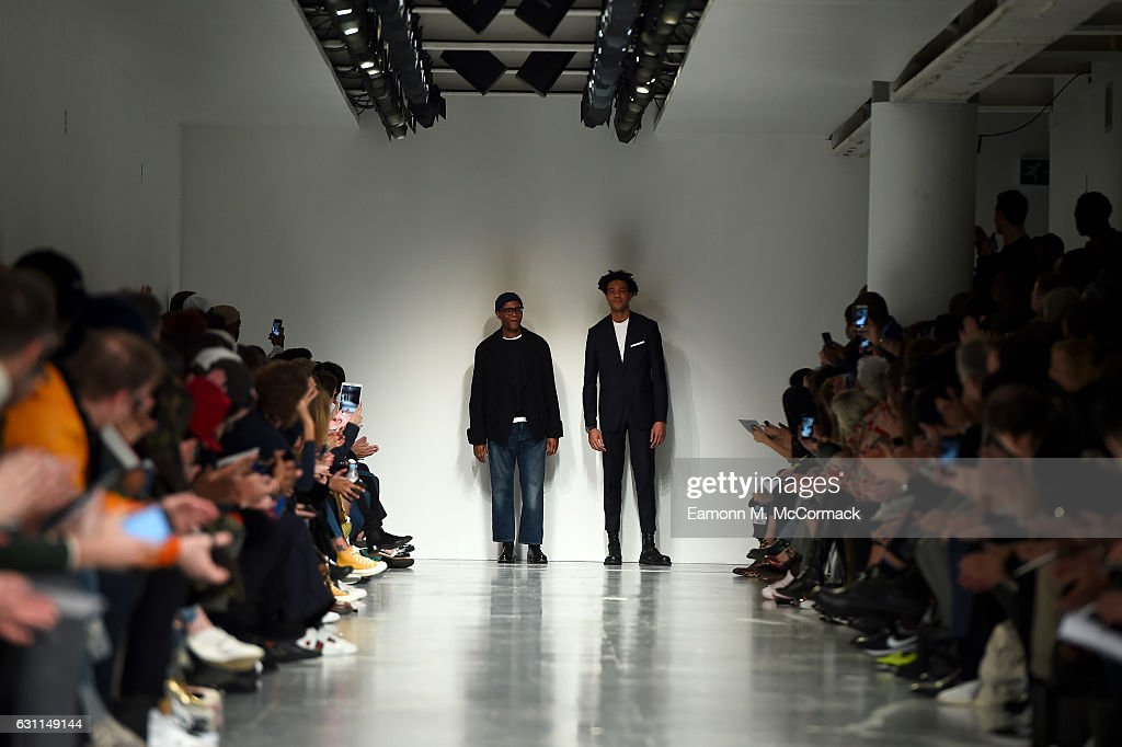 Designers Joe Casely-Hayford and Charlie Casely-Hayford salute the crowd following the Casely-Hayford show during London Fashion Week Men's January 2017 collections at BFC Show Space on January 7, 2017 in London, England.