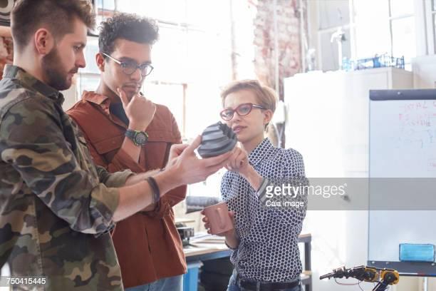 Designers meeting, examining prototype in workshop